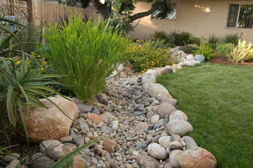 creek bed separating a garden and lawn