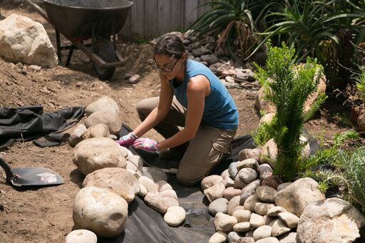 hand placing stones for creek bed